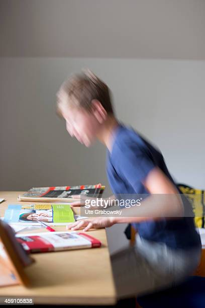 Hyperactive fourteenyearold boy sitting on his desk and doing homework on August 12 in Duelmen Germany Photo by Ute Grabowsky/Photothek via Getty...