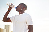 A portrait of a young black male drinking water after an exercise session.