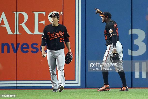 Hyun Soo Kim of the Baltimore Orioles and Adam Jones react in the seventh inning after a fan threw a beverage onto the field during the American...