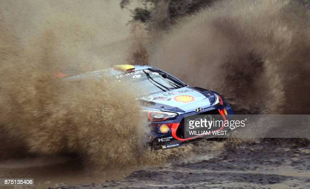 TOPSHOT Hyundai driver Andreas Mikkelsen of Norway powers through a water hazard on the first day of Rally Australia near Coffs Harbour on November...