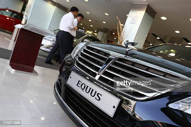 Hyundai Motor Co employees walk past an Equus luxury sedan at one of the company's dealerships in Seoul South Korea on Wednesday July 24 2013 Hyundai...