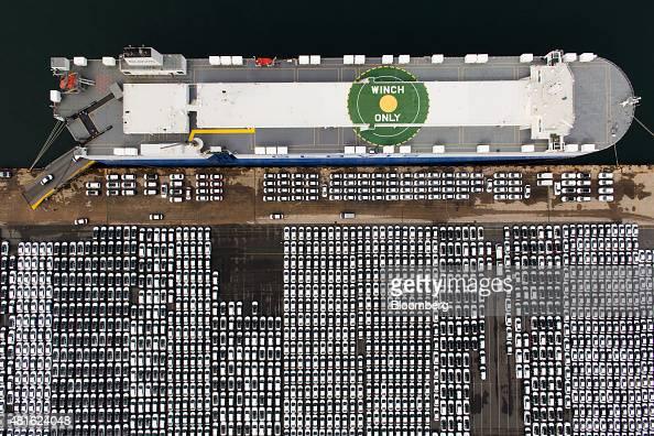 Hyundai Motor Co vehicles bound for export await shipment next to a Hyundai Glovis Co rollon/rolloff cargo ship at a port near Hyundai Motor's Ulsan...