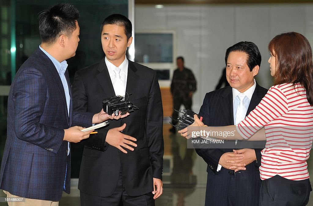 Hyung Jin Moon (L), the successor to Sun Myung Moon, the deceased founder of the Unification Church, with Park Sang-Kwon (R) the president of the church-invested Pyeonghwa Motors in North Korea, talks with members of the media on arrival at the border checkpoint at Dorasan in Paju on September 8, 2012, the route that leads to the Seoul-invested industrial estate in the North's Kaesong City. The youngest son and successor to Sun Myung Moon, the Unification Church's deceased founder, had a tearful reunion in North Korea with his aunt as they mourned Moon's death, a church official said.