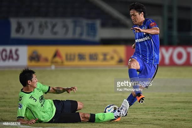 Hyungil Kim of Jeonbuk Hyundai Motors challenges Yasuhito Endo of Gamba Osaka during the AFC Champions League quarter final match between Gamba Osaka...