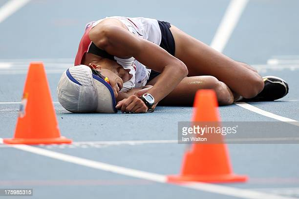 Hyunsub Kim of South Korea lies on the track after competing in the Men's 20km Race Walk final during Day Two of the 14th IAAF World Athletics...