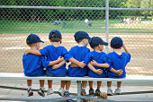 five little boys put their arms around each other befor their baseball game