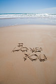i love you text written on brown sand ground low tide beach ocean seashore in Spain Europe
