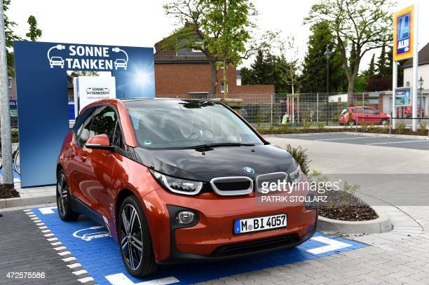 A BMW i3 electro car stands in front of a new charging station for electro cars on the carpark in front of an Aldi South supermarket discount store...