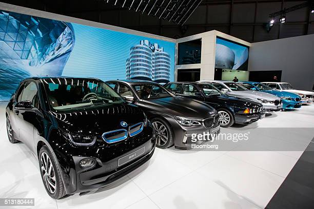 A BMW i3 plugin automobile left sits next to other automobiles produced by Bayerische Motoren Werke AG on the first day of the 86th Geneva...