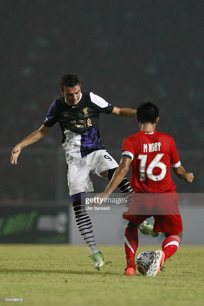 Iago Aspas (L) of Liverpool competes for the ball with M. Roby of Indonesia XI during the match between the Indonesia XI and Liverpool FC on July 20, 2013 in Jakarta, Indonesia.