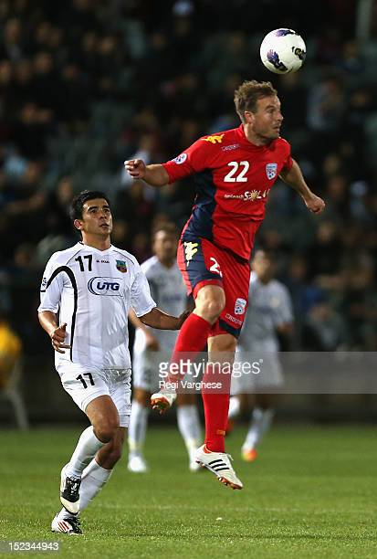 Iain Fyfe of Adelaide heads the ball while Murzoev Kamoliddin of Bunyodkor looks on during the AFC Champions League Quarter Final match between...