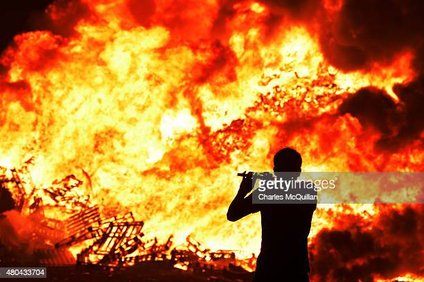 Iain McFarland an Orange bandsman plays his flute during the 11th night bonfire at the New Mossley housing estate on July 12 2015 in Belfast Northern...