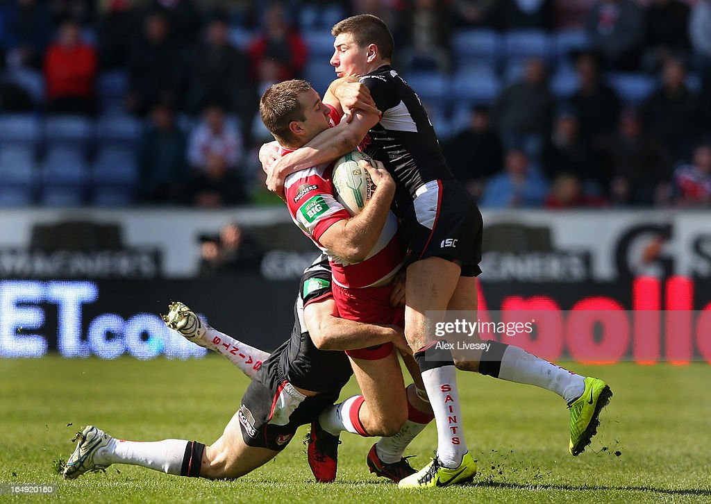 Iain Thornley of Wigan Warriors is tackled by Mark Percival of St Helens during the Super League match between Wigan Warriors and St Helens at DW Stadium on March 29, 2013 in Wigan, England.