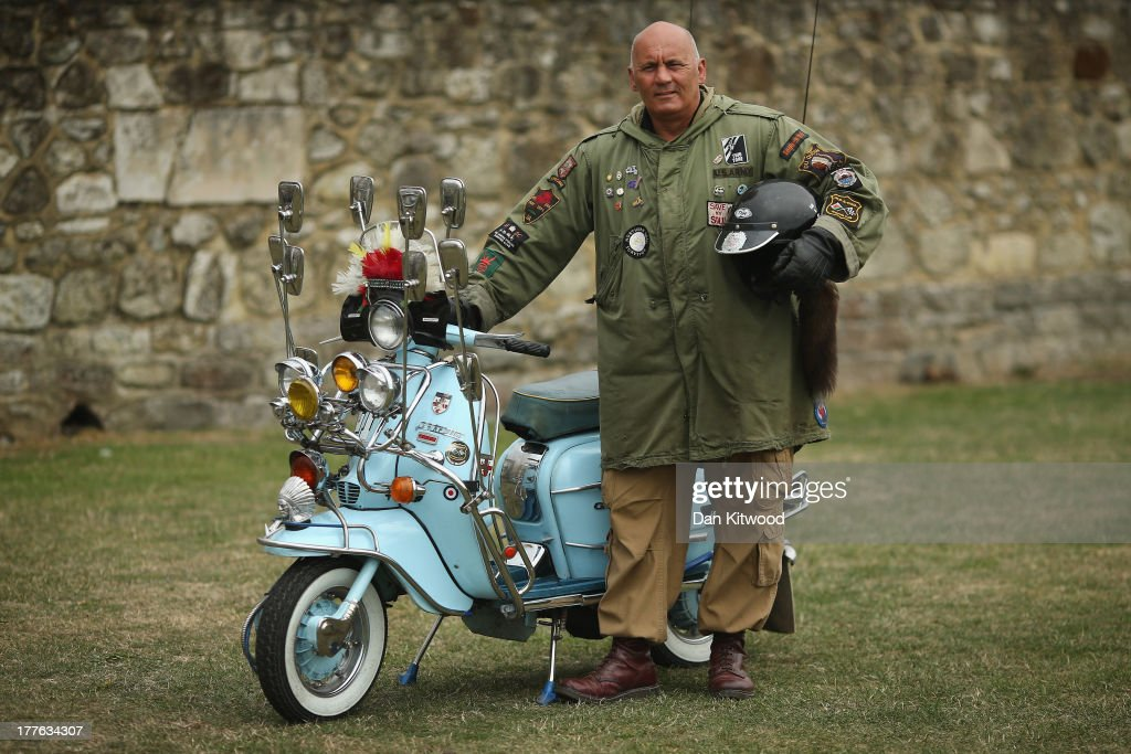 Ian Aviet of the Old School Scooter club in Cardif stands besides his 1962 LI 150 during the annual Isle of Wight Scooter Festival on August 25, 2013 in Ryde, England. The annual event, which is organized by the British Scooter Rally Association and The VFM Scooter Collective, attracts around 6000 riders each year and has been running since 1980. The scooter in 1960s Britain was a fashion statement and the often heavily customized bikes, usually an Italian Vespa or Lambretta, became synonymous with the Mod scene. They provided an inexpensive mode of transport and escapism to an upwardly mobile youth at a time when public transportation stopped early. The Vespa was depicted on the cover of The Whos Quadrophenia album in 1973.