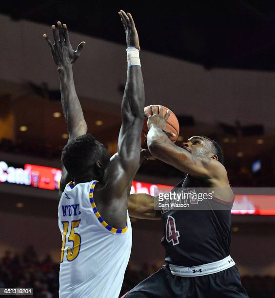 Ian Baker of the New Mexico State Aggies shoots gainst Fallou Ndoye of the Cal State Bakersfield Roadrunners during the championship game of the...