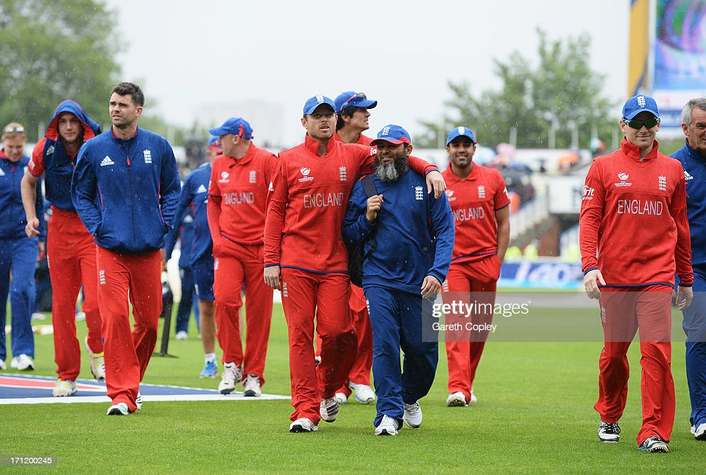 Ian Bell and England bowling coach Mushtaq Ahmed walk back to the dressing room with team mates after rain begins to fall prior to the ICC Champions...