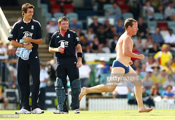 Ian Bell of England looks on as a pitch invader runs on to steal a bail during the tour match between the Australian PM's XI and England at Manuka...