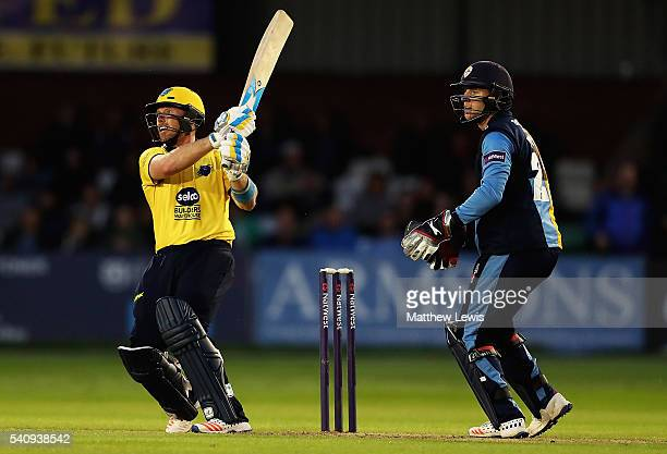 Ian Bell of Warwickshire hits the ball towards the boundary as Tom Poynton of Derbyshire looks on during the NatWest T20 Blast match between...