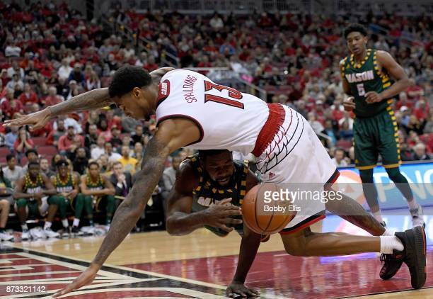 Ian Boyd of the George Mason Patriots passes the ball under Ray Spalding of the Louisville Cardinals during the first half of the game between the...