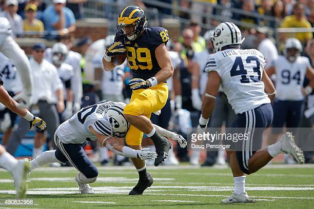 Ian Bunting of the Michigan Wolverines makes a reception as Michael Wadsworth of the Brigham Young Cougars makes the tackle at Michigan Stadium on...
