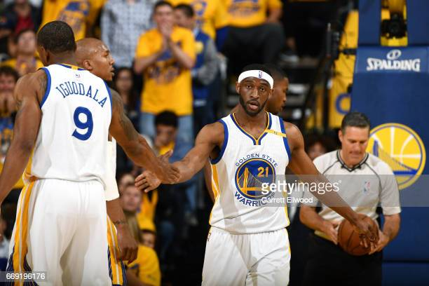 Ian Clark and Andre Iguodala of the Golden State Warriors high five each other during the game against the Portland Trail Blazers during the Western...