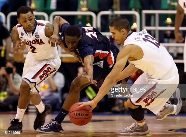 Ian Clark of the Belmont Bruins drives through Mark Lyons and Nick Johnson of the Arizona Wildcats in the first half during the second round of the...