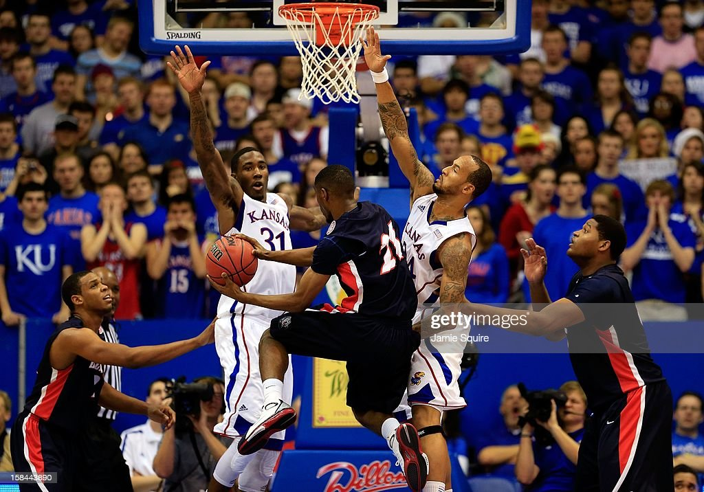 Ian Clark #21 of the Belmont Bruins is stopped by Jamari Traylor #31 and <a gi-track='captionPersonalityLinkClicked' href=/galleries/search?phrase=Travis+Releford&family=editorial&specificpeople=5628041 ng-click='$event.stopPropagation()'>Travis Releford</a> #24 of the Kansas Jayhawks during the game at Allen Fieldhouse on December 15, 2012 in Lawrence, Kansas.