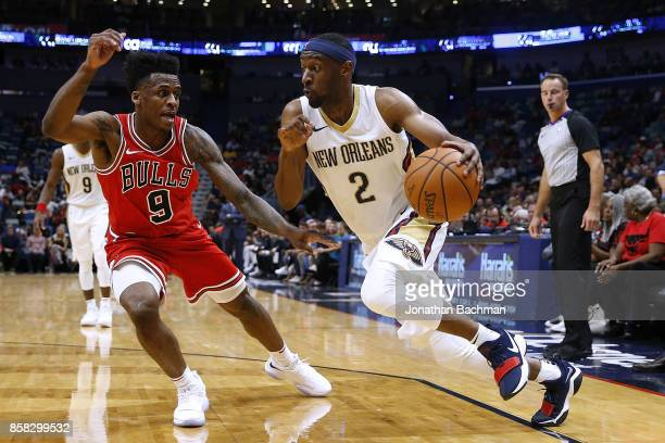 Ian Clark of the New Orleans Pelicans drives against Antonio Blakeney of the Chicago Bulls during a preseason game at the Smoothie King Center on...