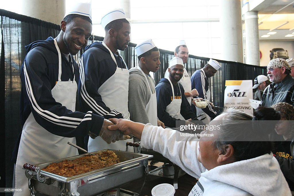Ian Clark #21 of the Utah Jazz greets a fan during the we care-we share Thanksgiving Dinner feeding the homeless at EnergySolutions Arena on November 27, 2013 in Salt Lake City, Utah.
