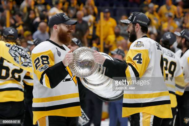 Ian Cole and Justin Schultz of the Pittsburgh Penguins of the Pittsburgh Penguins celebrate with the Stanley Cup trophy after defeating the Nashville...