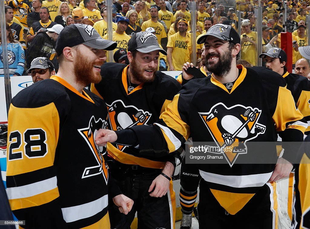 Ian Cole #28 celebrates with Tom Kuhnhackl #34 and Justin Schultz #4 of the Pittsburgh Penguins after a 2-1 win over the Tampa Bay Lightning in Game Seven of the Eastern Conference Final during the 2016 NHL Stanley Cup Playoffs at Consol Energy Center on May 26, 2016 in Pittsburgh, Pennsylvania.