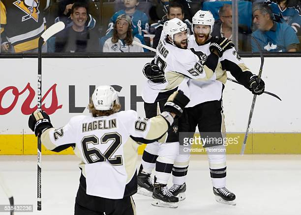 Ian Cole of the Pittsburgh Penguins celebrates with Kris Letang and Carl Hagelin after scoring against the San Jose Sharks in the first period of...