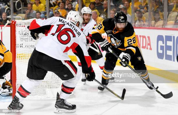 Ian Cole of the Pittsburgh Penguins handles the puck against Clarke MacArthur of the Ottawa Senators in Game Seven of the Eastern Conference Final...