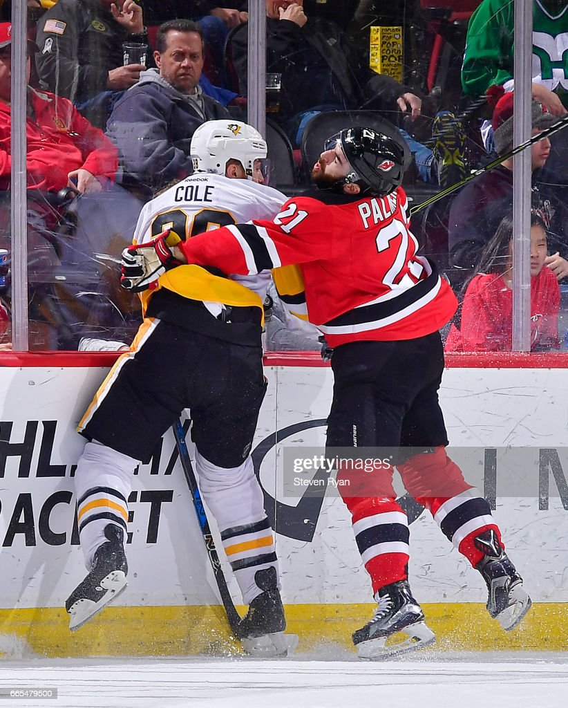 Ian Cole #28 of the Pittsburgh Penguins is checked into the boards by Kyle Palmieri #21 of the New Jersey Devils during an NHL game at Prudential Center on April 6, 2017 in Newark, New Jersey.