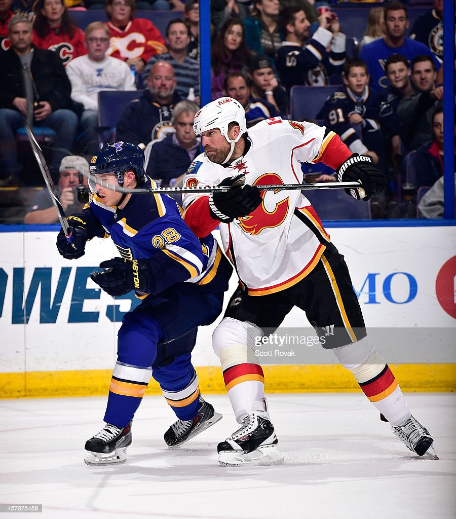 Ian Cole of the St Louis Blues and Brian McGrattan of the Calgary Flames battle for position on October 11 2014 at Scottrade Center in St Louis...