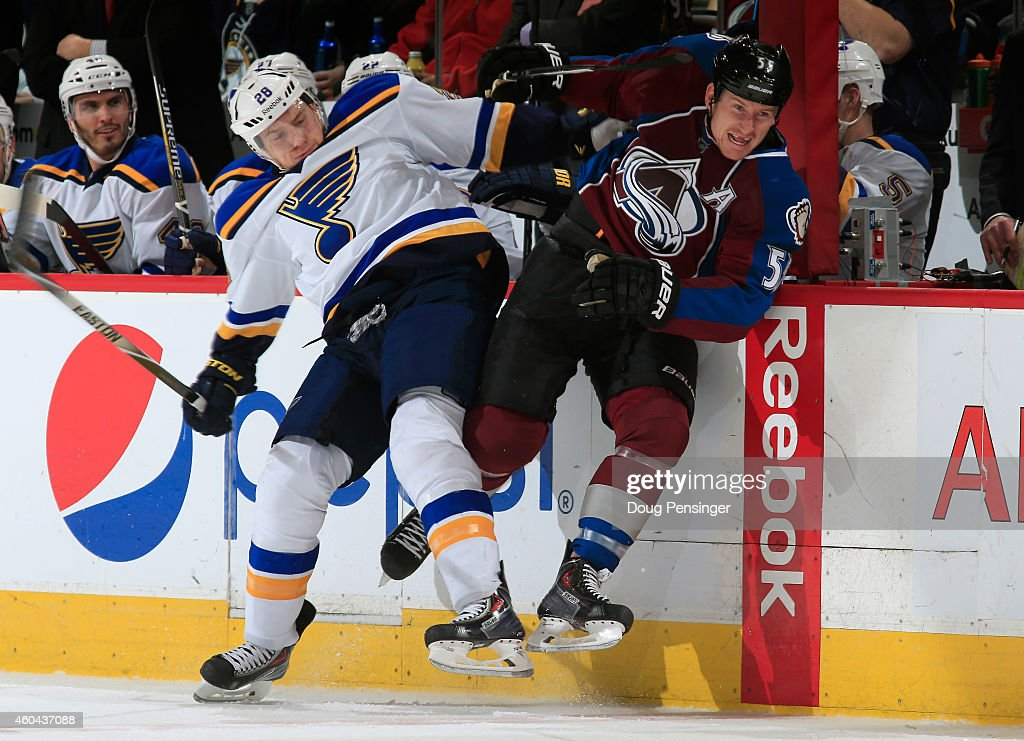 Ian Cole of the St Louis Blues and Cody McLeod of the Colorado Avalanche collide as they pursue the puck at Pepsi Center on December 13 2014 in...