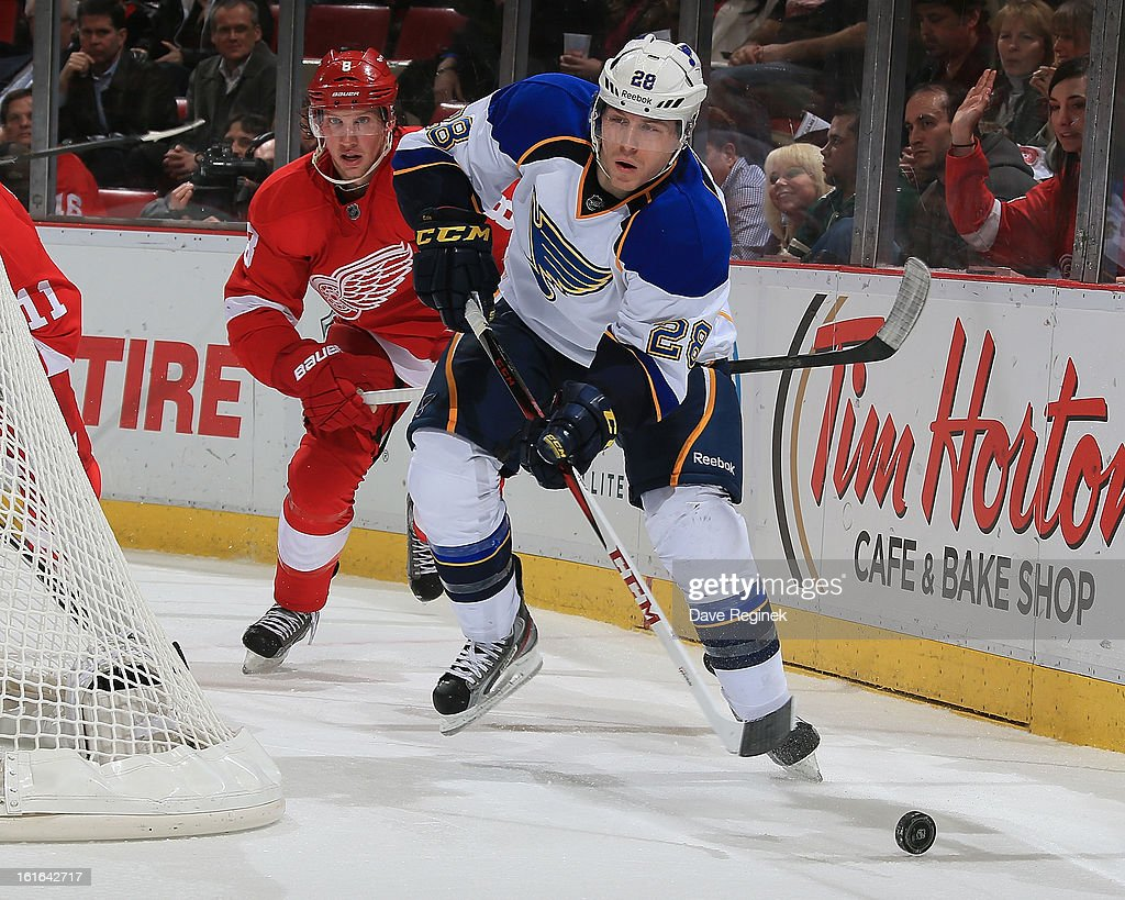 Ian Cole #28 of the St Louis Blues passes the puck in front of Justin Abdelkader #8 of the Detroit Red Wings during a NHL game at Joe Louis Arena on February 13, 2013 in Detroit, Michigan. The Blues won in overtime 4-3