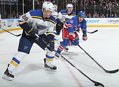 Ian Cole of the St Louis Blues skates with the puck against Tanner Glass of the New York Rangers at Madison Square Garden on November 3 2014 in New...