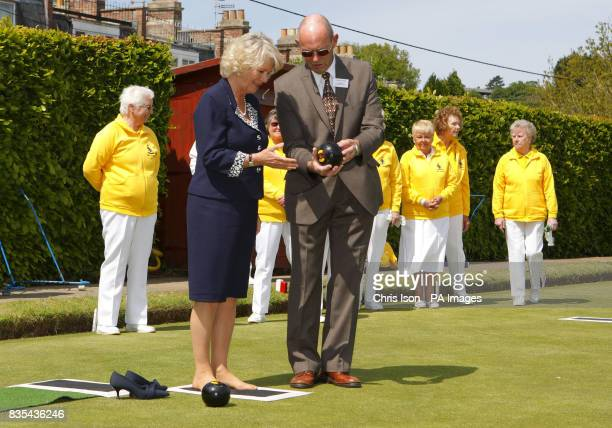 Ian Collier Chairman of the Box Bowling Club looks on as The Duchess of Cornwall takes her first attempt at bowling after first removing her shoes...