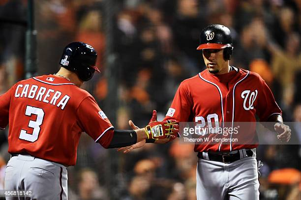 Ian Desmond celebrates with Asdrubal Cabrera of the Washington Nationals after scoring on a RBI double by Bryce Harper in the fifth inning against...