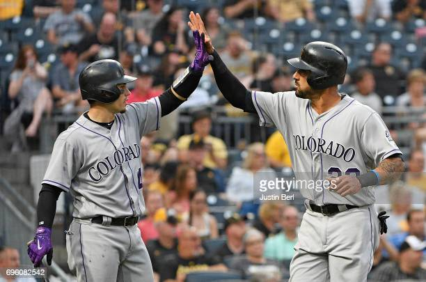 Ian Desmond of the Colorado Rockies high fives with Tony Wolters after coming around to score on an RBI single by Trevor Story in the fifth inning...