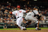 Ian Desmond of the Washington Nationals avoids the tag of Matt Wieters of the Baltimore Orioles as he scores a run in the eighth inning during an...