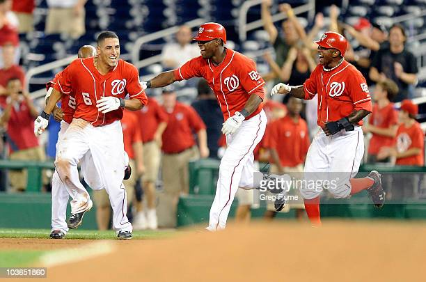 Ian Desmond of the Washington Nationals celebrates with Roger Bernadina and Nyjer Morgan after driving in the game winning run in the thirteenth...