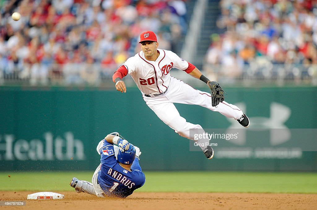 Ian Desmond of the Washington Nationals jumps over Elvis Andrus of the Texas Rangers after forcing him out at second base in the third inning at...