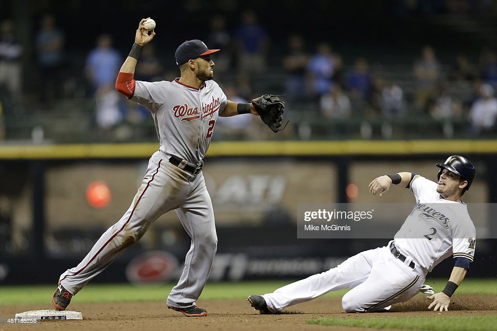 Ian Desmond #20 of the Washington Nationals overthrows to first base while Scooter Gennett #2 of the Milwaukee Brewers slides into second base in the bottom of the fifteenth inning at Miller Park on June 24, 2014 in Milwaukee, Wisconsin.