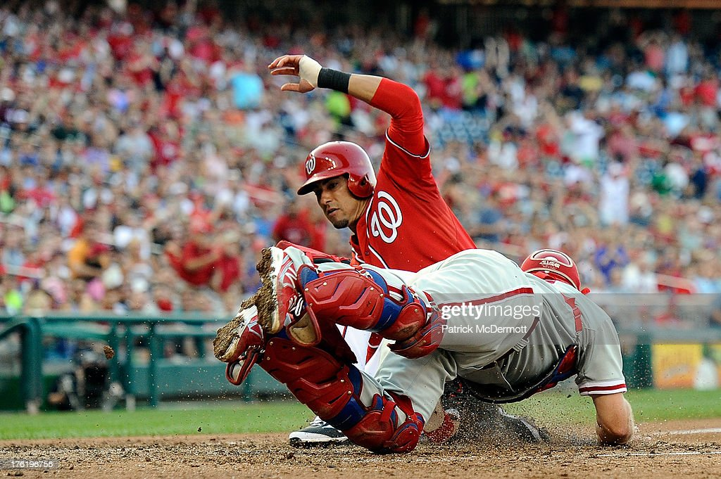<a gi-track='captionPersonalityLinkClicked' href=/galleries/search?phrase=Ian+Desmond&family=editorial&specificpeople=835572 ng-click='$event.stopPropagation()'>Ian Desmond</a> #20 of the Washington Nationals slides safely into home plate past <a gi-track='captionPersonalityLinkClicked' href=/galleries/search?phrase=Erik+Kratz&family=editorial&specificpeople=809194 ng-click='$event.stopPropagation()'>Erik Kratz</a> #31 of the Philadelphia Phillies in the fifth inning during a game at Nationals Park on August 11, 2013 in Washington, DC.