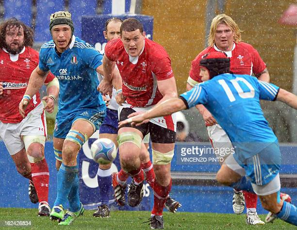 Ian Evans of Wales runs with Italians Kris Burton and Francesco Minto during their Six Nations rugby match at the Olympic stadium on February 23 2013...