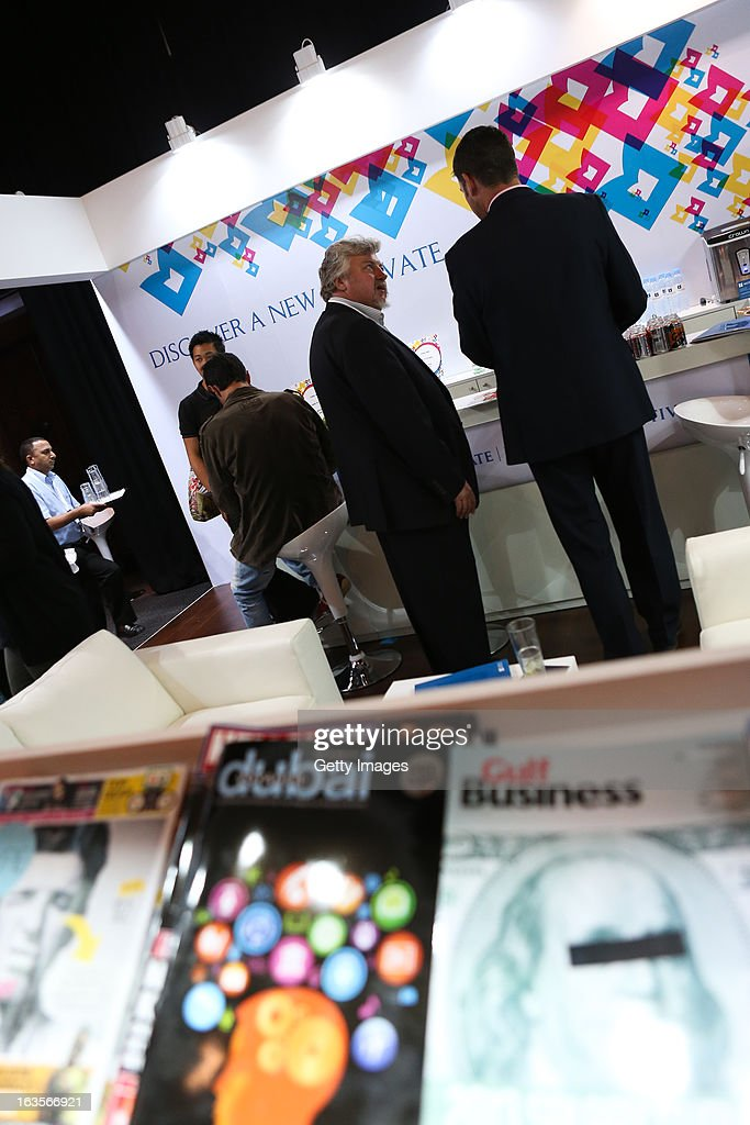 Ian Fairservice, Founder and CEO of Motivate Publishing(left of centre) chats with a guest on the Motivate Publishing stall at the Madinat Jumeirah on March 12, 2013 in Dubai, United Arab Emirates.
