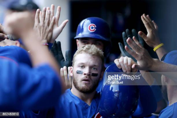 Ian Happ of the Chicago Cubs celebrates with teammates after scoring a run in the eighth inning against the Milwaukee Brewers at Miller Park on...