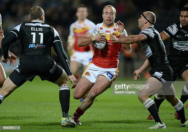 Ian Henderson of Catalan Dragons looks to get past Gareth Ellis and Danny Houghton of Hull FC during the Super League match between Hull FC and...